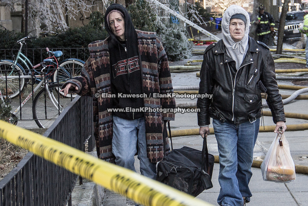 BROOKLINE, MASS.- Residents of The Empire Bulding on Beacon Street carry their remaining possessions after being displaced by a four alarm fire on January 16, 2012.