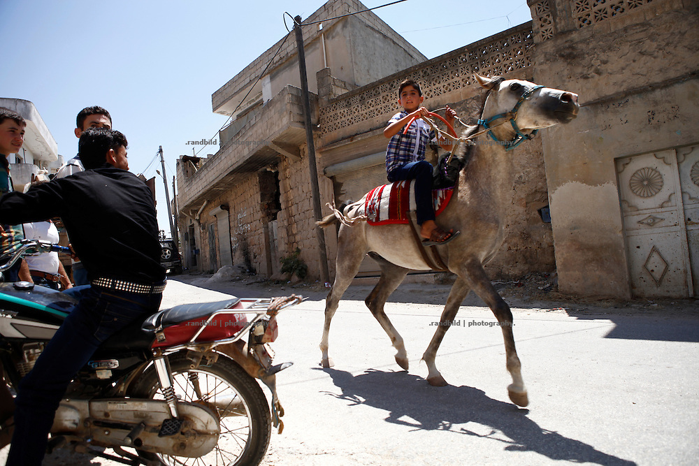 A teenager furiously rides on a horse through the streets of Koreen.<br /> _ _ _ <br /> Idlib Interim - Challenging life without central government in the village of Koreen (Idlib Province, Syria)<br /> Koreen joint the syrian uprisung to ouster president Bashar al-Assad at a very early stage in 2011. It has been scene of Army attacks and heavy shelling since 2012. In the course of the fightings the village of a few thousend inhabitants was almost abandoned as barrel bomb campaings commited by the regime pounded Koreen. But since regime forces retreated to few bases remaining in Idlib province people returned home to establish a new and almost unregulated economic, social and community life. The regimes power has no affect and can&acute;t reach them anymore. On the other hand a new government isn&acute;t established yet and not in sight at all. Koreen is free to make its way.