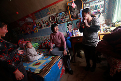 Chinese 'yaodong' or cave home dwellers Bei Fenglan (2-R) shares a light moment with her daughter Wang Qiuxia (L), daughter-in-law Pei Jimei (R) and one-year-old grandson Wang Xi while resting in their cave home on the top of a mountain in Yichuan county of Yan'an city, Shaanxi Province China, 06 November 2012. Bei's family of six are apple farmers and have seen growing difficulties in making ends meet from their produce, prompting her 38-year-old son to leave home to work as a construction worker to help support the family. The 'yadong' or cave dwellings are typical in the plateaus of northern China in Shaanxi Province where many of Yan'an's rural population still live in. They are mostly carved out from the yellow earth of the Loess hillsides and are about seven to eight metres deep with height and width of three metres. Former Communist leader Mao Zedong and his comrades are known to have hid in these cave homes during the civil war between the communists and nationalists in 1936 to 1948 as they battle the Kuomintang forces. China's new leaders slated to take over during the 18th National Congress beginning on 08 November are likely to face mounting pressures to tackle the country's rising income inequalities between urban and rural areas that are often the source of simmering resentment and growing unrests on the grassroot level.