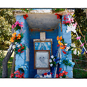 """SHOT 2/7/15 12:04:30 PM - A roadside capilla in the mountains just outside of Col La Yerbabuena, Mexico and featuring Nuestra Señora de Guadalupe as well as pictures of loved ones, flowers and personal effects. The Virgin of Guadalupe has symbolized the Mexican nation since Mexico's War of Independence. Our Lady of Guadalupe (Spanish: Nuestra Señora de Guadalupe) is a celebrated Catholic icon of the Virgin Mary also known as the Virgin of Guadalupe (Spanish: Virgen de Guadalupe). The Lady of Guadalupe is of significant importance to Mexican Catholics and has been given the titles of """"Queen of Mexico"""", """"Empress of the Americas"""", and """"Patroness of the Americas"""". Roadside capillas, or tiny chapels, are common along the roads and highways of Mexico which is heavily Catholic and are often dedicated to certain patron saints or to the memory of a loved one that has passed away. Often times they contain prayer candles, pictures, personal artifacts or notes. (Photo by Marc Piscotty / © 2015)"""
