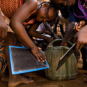 Children clean their chalk boards with water during class at the Kabiline I Primary school in the village of Kabiline, Senegal on Wednesday June 13, 2007...
