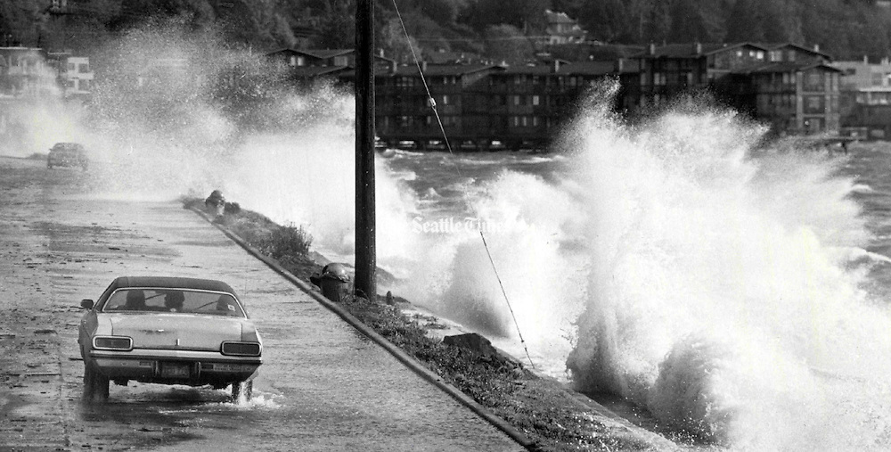 A motorist drives down Beach Drive S.W. near Alki Point as heavy winds and high tide create a pounding surf. (Craig Fuji / The Seattle Times, 1984)