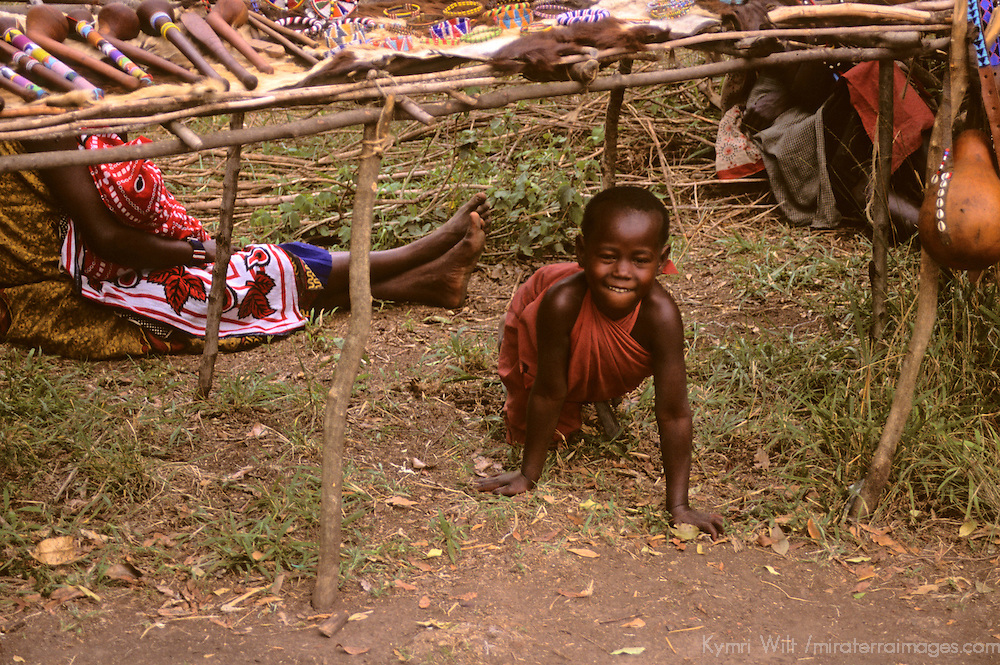 Africa, Kenya, Maasai Mara. A young Maasai boy sneaking out at Olanana in the Maasai Mara.