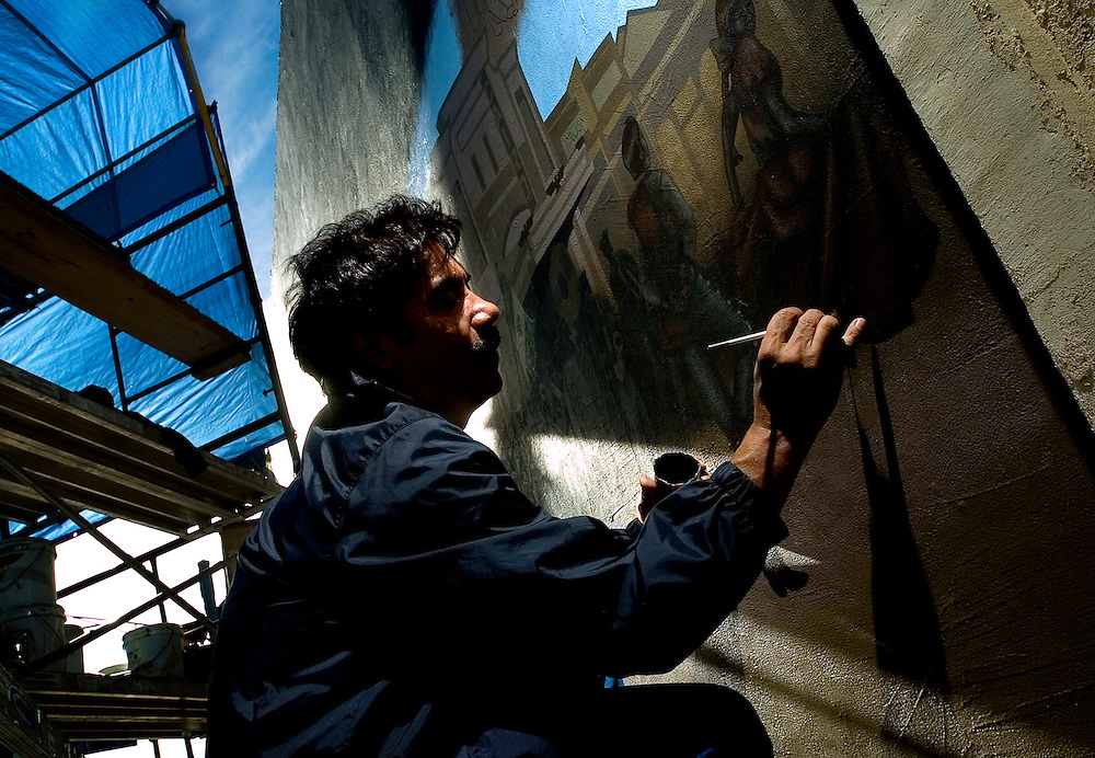 """100807      Brian Leddy.Ric Sarracino works on a mural entitled """"Gallup Hispanics"""" on Coal Street near the First Street intersection on Monday. Sarracino was commissioned by the city to paint the 23 by 12 foot mural, which he estimates will take him another two months to complete. The mural, which depicts scenes of Hispanic life, is the first of its kind for the city."""