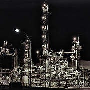 Chemical plant Lake Charles, LA at night with all of the plant safety lights on. Work area is made of steel girders, walkways, bridges, ladders and hand rails. Multiple towers are connected to the main stair structure.