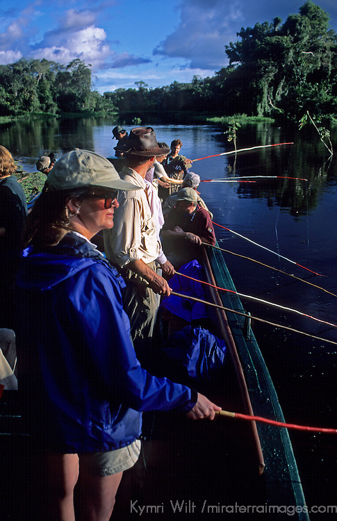 South America, Peru, Amazon River. Tour group fishing for pirranhas.