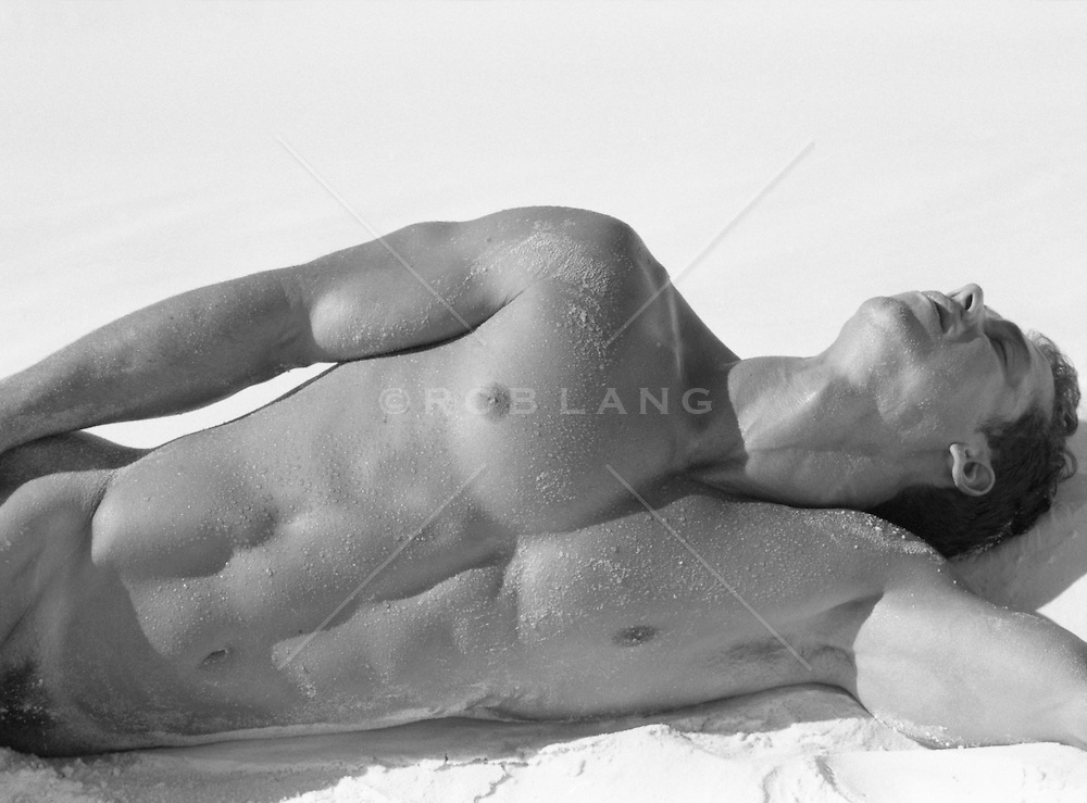 upper body of nude man resting on sand in White Sands, NM