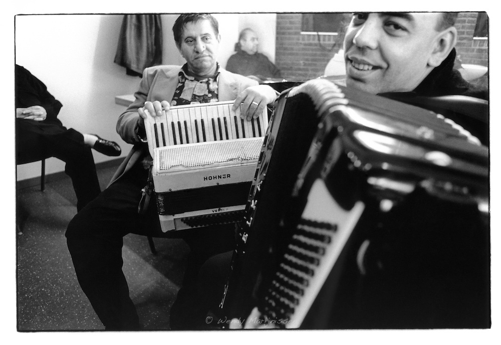 Members of Taraf de Haïdouks backstage in their dressing room playing on the accordion. C.C. de Warande, Turnhout, Belgium, 2002