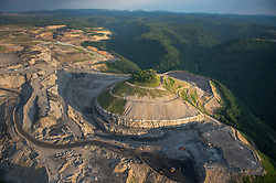 A bird's-eye view of the mountaintop-removal mine that emptied Lindytown, West Virginia. Mountaintop Removal is a method of surface mining that literally removes the tops of mountains to get to the coal seams beneath. It is the most profitable mining technique available because it is performed quickly, cheaply and comes with hefty economic benefits for the mining companies, most of which are located out of state. It is the most profitable mining technique available because it is performed quickly, cheaply and comes with hefty economic benefits for the mining companies, most of which are located out of state. Many argue that they have brought wage-paying jobs and modern amenities to Appalachia, but others say they have only demolished an estimated 1.4 million acres of forested hills, buried an estimated 2,000 miles of streams, poisoned drinking water, and wiped whole towns from the map.