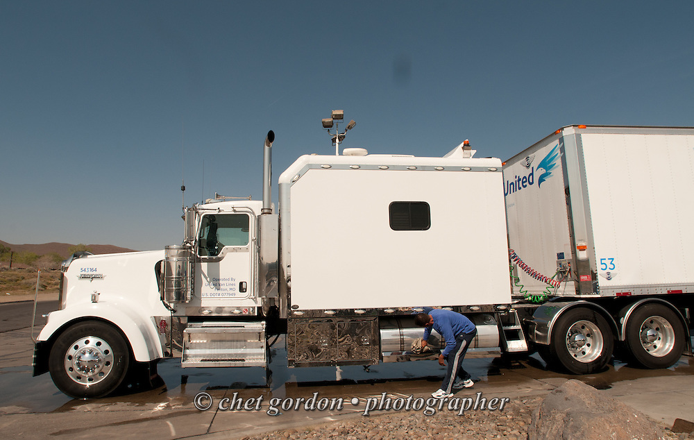 Over the road driver Jose Williams wipes off his fuel tanks after a truckwash in Fenley, NV on Monday, April 20, 2015. Williams, a cross country trucker with a national household moving company, made several delivery stops in central California's Bay Area during the week with loads that originated in Virginia on April 16th.  © Chet Gordon/THE IMAGE WORKS