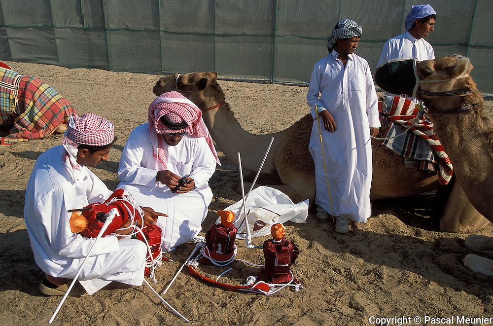 QATAR. Doha. Camels races. Robots...Previously, the jockeys were African children, ?abandoned? once they were too tall thus mobilizing NGOs. To regulate the problem, the Emir replaced them by robots, connected to the trainer by a walkie talkie to hurl at the camel. A robot costs only 475 euros, but a race camel around 600.000 euros.