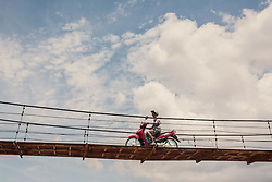 A motorbike crosses a wooden bridge over  canal in the Mekong Delta, Vietnam, Southeast Asia.