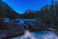 The Natural Bridge waterfal on the Kicking Horse River, in Yoho National Park, in the deepening twilight on June 7, 2016 with the stars beginning to appear. I painting the foreground water with a quick pass of an LED light. <br /> <br /> This is a single 25-second exposure with the 20mm lens at f/2.5 and Nikon D750 at ISO 640.