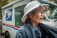 """Letter carrier Connie Gumataotao delivers mail on a rainy day in Calistoga.  """"I've been delivering mail in Calistoga for 19 years...I know where everyone lives."""""""