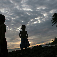 A young boy and girl at dusk on the beach on the island of Kiribati in the South Pacific. The islands, and their way of life, is endangered by rising sea water levels which are eroding the fragile atoll, home to approximately 92,000 people.