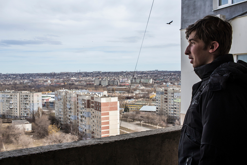 LUHANSK, UKRAINE - MARCH 15, 2015: Pavel Pavlov looks out from the balcony of an apartment building near his mother's apartment in Luhansk, Ukraine. CREDIT: Brendan Hoffman for The New York Times