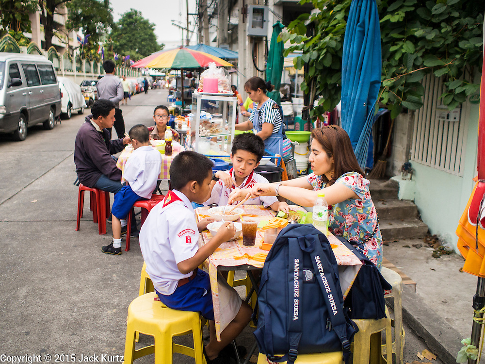 18 FEBRUARY 2015 - BANGKOK, THAILAND: People eat food from street vendors on Soi Thetsaban Sai 1 in the Kudeejeen neighborhood in Bangkok. Santa Cruz church was established in 1770 and is the heart of the community. It is one of the oldest and most historic Catholic churches in Thailand. The church was originally built by Portuguese soldiers allied with King Taksin the Great. Taksin authorized the church as a thanks to the Portuguese who assisted the Siamese during the war with Burma. Most of the Catholics in the neighborhood trace their family roots to the original Portuguese soldiers who married Siamese (Thai) women. There are about 300,000 Catholics in Thailand in about 430 Catholic parishes and about 660 Catholic priests in Thailand. Thais are tolerant of other religions and although Thailand is officially Buddhist, Catholics are allowed to freely practice and people who convert to Catholicism are not discriminated against.   PHOTO BY JACK KURTZ
