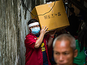 03 SEPTEMBER 2016 - BANGKOK, THAILAND:   Bangkok city workers carry out the belongings of a Pom Mahakan resident who agreed to leave the historic Bangkok community during an operation to evict Pom Mahakan residents Saturday. Hundreds of people from the Pom Mahakan community and other communities in Bangkok barricaded themselves in the Pom Mahakan Fort to prevent Bangkok officials from tearing down the homes in the community Saturday. The city had issued eviction notices and said they would reclaim the land in the historic fort from the community. People prevented the city workers from getting into the fort. After negotiations with community leaders, Bangkok officials were allowed to tear down 12 homes that had either been abandoned or whose owners had agreed to move. The remaining 44 families who live in the fort have vowed to stay.    PHOTO BY JACK KURTZ