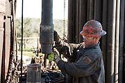 Cuero, Texas. Fracking brought a huge oil boom to Dewitt County in Texas...Ein Oel-Arbeiter schraubt auf Bohrturm Rohre zusammen. Sie bohren 4000 Fuss in die Tiefe, und 2000 Fuss in die horizontale Richtung. Der Bohrturm gehört dem amerikanischen Oel-Milliardaer George Bishiop...© Stefan Falke www.stefanfalke.com.Unterwegs mit Peter Hossli.