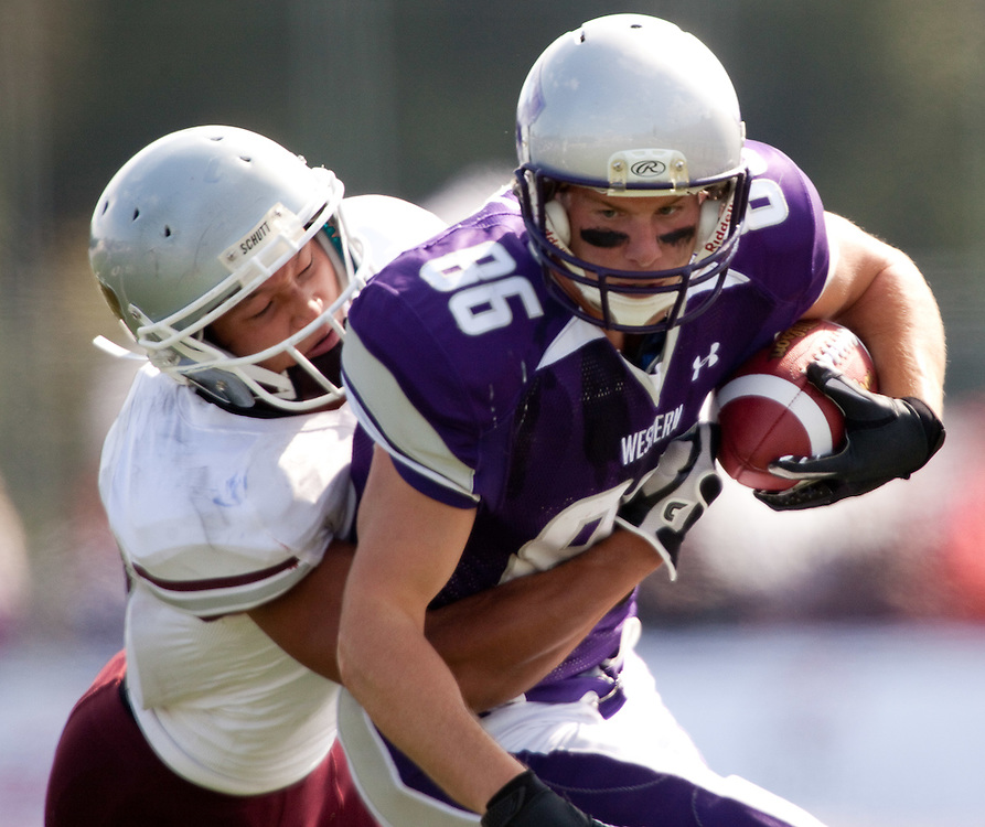 London, ONT.; September 17, 2011 -- Western's Zach Bull is tackled by Ottawa's Soonbum Cha  during the Mustang's 41-13 victory over the Gee Gees at TD Waterhouse Stadium in London, Ontario, September 17, 2011.  <br /> <br /> (GEOFF ROBINS/ Ottawa Citizen
