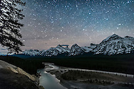 The autumn stars of the watery constellations of Capricornus, Aquarius, Piscis Austrinus, and Cetus over the Athabasca River and the peaks of the Continental Divide, from the Athabasca River Viewpoint (the &ldquo;Goats and Glaciers&rdquo; viewpoint) on the Icefields Parkway, Jasper National Park, Alberta. Illumination is from starlight. Thin cloud provides the natural glows around the stars.<br />