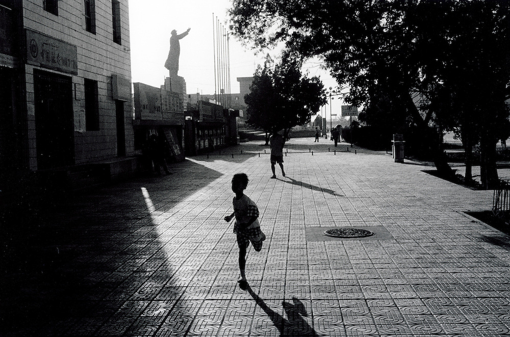 Xinjiiang Uygur Autonomous region. Kashgar. Boy runs in Renmin Square in front of the worlds largest Mao statue in Kashgar.