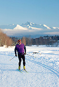 USA, Alaska, Anchorage, A man enjoys a spectacular winter day by cross-country skiing along Westchester Lagoon near downtown Anchorage.