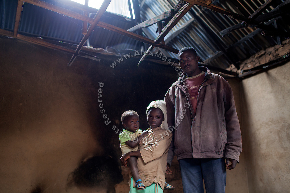 A father (right) and his daughter - carrying a younger sibling - are standing in their destroyed home in Kakuruk village, Gashish district, in the local government of Barkin Ladi, near Jos, Plateau State, Nigeria. The village, inhabited by Christians from the Berom tribe, has received various attacks by neighbouring Muslim Fulani - a nomadic cattle-herder tribe non-indigenous to Plateau - with the last one on 7th July, 2012, when more than 30 houses were demolished and 8 Christian villagers killed.