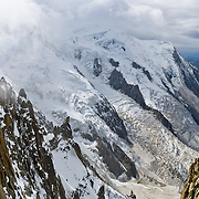 """Dôme du Goûter (center 14,121 feet or 4304 meters) is a shoulder of massive Mont Blanc (15,782 feet elevation) covered with massive glaciers such as Glacier des Bossons, seen from Aiguille du Midi, Chamonix, France, Europe..  Panorama stitched from 2 overlapping images. One of 17 photos published in Ryder-Walker Alpine Adventures """"Inn to Inn Alpine Hiking Adventures"""" Catalog 2006."""