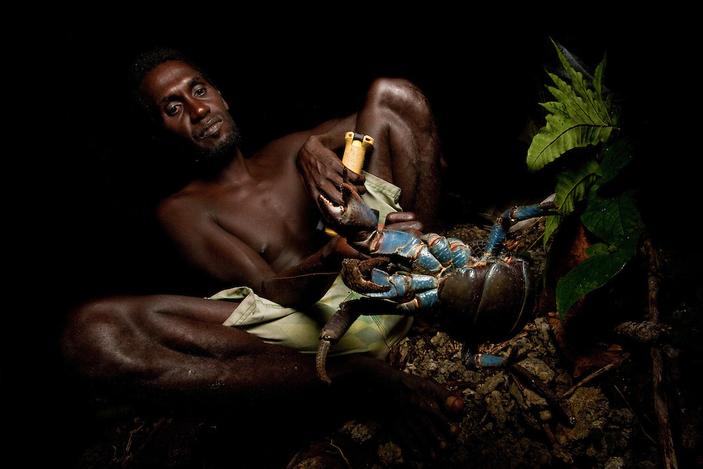 A local man holds a coconut crab, subject to a monitoring program on Tetapare