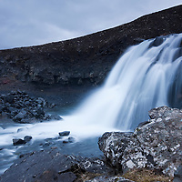 Iceland, Hvalfordur, Blurred image of waterfall along Hvalford on spring evening