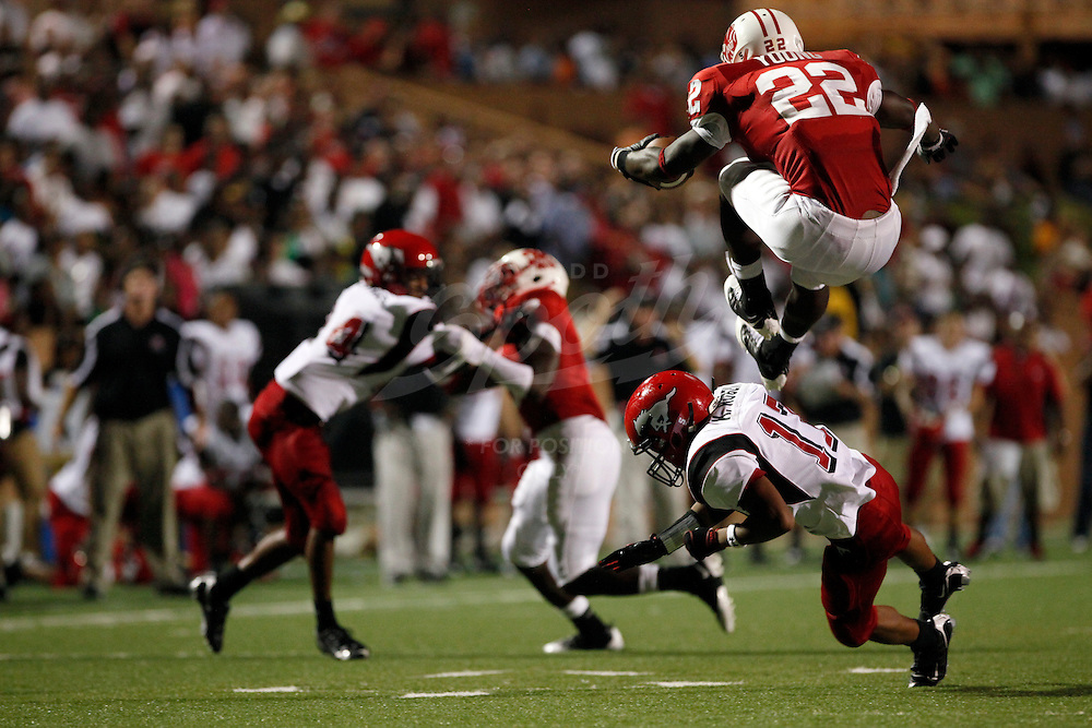 Katy running back Donovonn Young, 22, leaps over defenders, during the week 0 matchup between the North Shore High School Mustangs and the Katy High School Tigers at Rhodes Stadium in Katy, Texas. The Tigers won the game 7-9. (Todd Spoth/HCN)