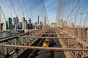 A yellow cab crosses Brooklyn Bridge in New York