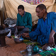 A man eating a breakfast of watery porridge in a tent at the Mbera camp for Malian refugees in Mauritania on 2 March 2013. The majority of the camp's residents are accustomed to a staple diet of goat, camel or cow's milk and meat, but the UNHCR-provided rations are of rice and cereal - malnutrition is a growing concern, particularly amongst under fives. Many refugees sell or barter their rations to try and obtain powdered milk and meat for their families.