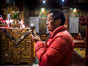 17 MARCH 2017 - KATHMANDU, NEPAL: A man prays in a monastery near Boudhanath Stupa in Kathmandu. The stupa is the holiest site in Nepali Buddhism. It is also the center of the Tibetan exile community in Kathmandu. The Stupa was badly damaged in the 2015 earthquake but was one of the first buildings renovated.     PHOTO BY JACK KURTZ