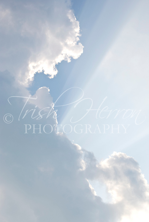 Rays of sun shine over a blue sky from behind cumulus clouds.
