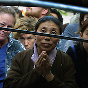 (Center to right) Chozom Myishar and her daughter Tsokyi peer between risers to get a view of the Dalai Lama in Pioneer Square. They came in from Seattle because they haven't seen him for 3 years and this visit is very important to them.
