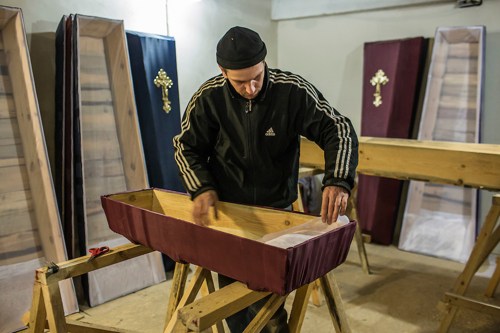 Pavel Bocharov builds a casket for Yana Myasischeva, a one-year-old girl who was killed on January 27 by a shelling on February 3, 2015 in Donetsk, Ukraine. The city government provides basic but free or low-cost caskets for victims of shelling or others who are no longer able to afford funeral expenses, the demand for which has increased significantly in past weeks as violence has flared once again.
