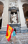 A pilgrim carrying a Spanish flag walks past a statue of St. Matthew inside the Basilica of St. John Lateran in Rome, Italy. (Sam Lucero photo)
