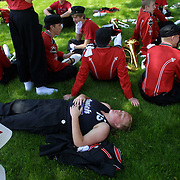 Exhausted band members from MOC Floyd Valley High School rest in the shade after marching over 4 miles in the annual Orange City .Tulip Festival in Orange City, Iowa, USA.  Holding to their Dutch traditions, the band members march in wooden shoes.  The MOC-Floyd Valley High School band has won numerous state and national awards for their excellence and is made up 180 of the school's 360 students.  The band members develop a strong bond during the year.  This event took place in April of 2004.