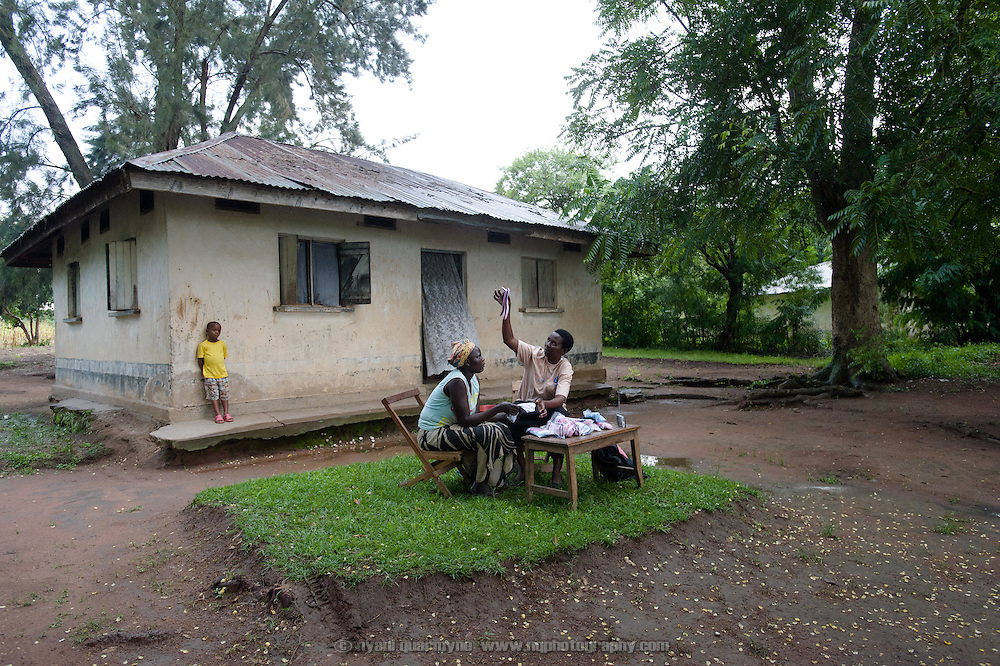 """Lovisa Wankya, a teacher and an Afripads dealer, in front of her home near Tororo in Eastern Uganda, explaining to Caroline Adongo how Afripads should be dried in the sun, on 1 August 2014. Having heard of Afripads and """"Madam Wankya"""" on the radio, Caroline was interested in them, but didn't know how to contact Lovisa. She happened to be passing by, and was excited to meet """"Madam Wankya"""" and learn about Afripads. She decided to buy two kits, one for herself and one for her daughter. (Afripads are reusable fibre sanitary pads that are having a revolutionary impact on menstrual hygiene management, particularly amongst girls and women who cannot afford expesive disposable pads, and who previously had to use rags, cotton wool or toilet paper.)"""