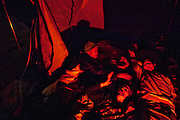Campers stay warm in a tent heated by a propane burner at the SafeGround camp in Sacramento, Calif., January 13, 2011.
