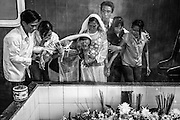 Family members give final sorrowful goodbye to their mother as her coffin is lowered for cremation at a mortuary in Ho Chi Minh City, Vietnam.