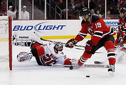 Oct 17, 2009; Newark, NJ, USA; Carolina Hurricanes goalie Cam Ward (30) makes a rolling save on New Jersey Devils center Travis Zajac (19) during the second period at the Prudential Center.