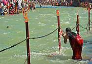 A girl splashes the River Ganges sacred water onto her face.