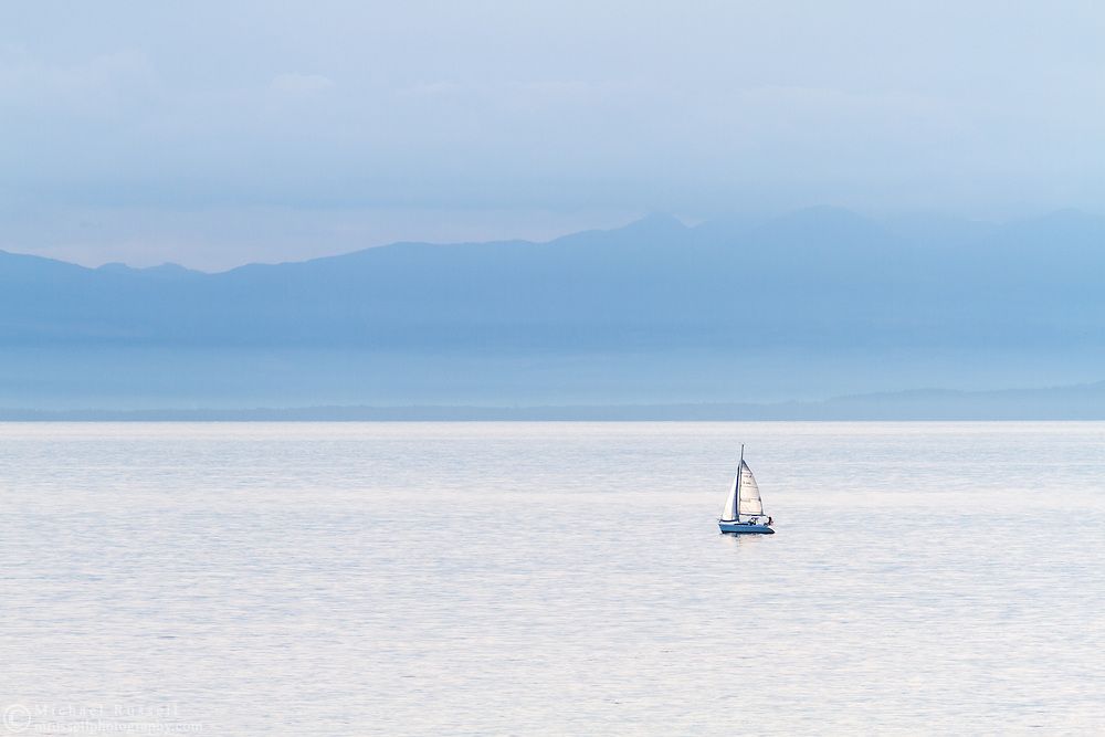 A small sailboat (a Hunter 280 Sailboat) in the Salish Sea (Georgia Straight) west of Vancouver.  Photographed from Juniper Point at  Lighthouse Park in West Vancouver, British Columbia, Canada. The mountains in the background are located on Vancouver Island.