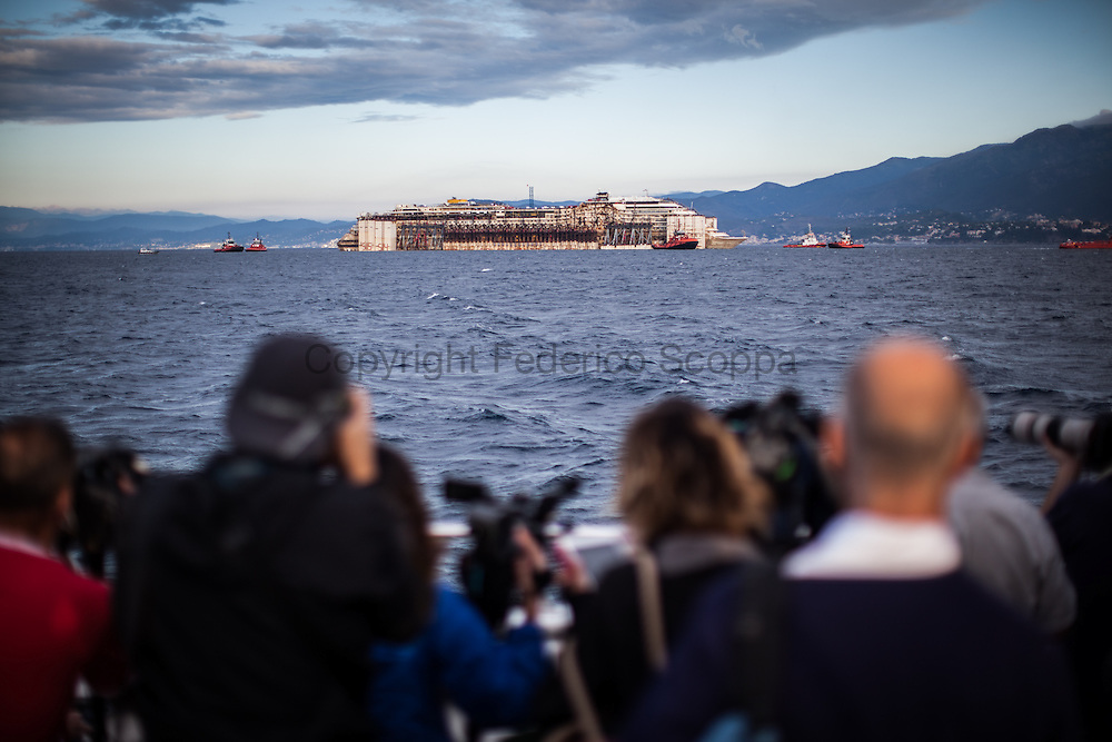 A press boat reaches the Costa Concordia convoy just outside the Genoa Voltri port