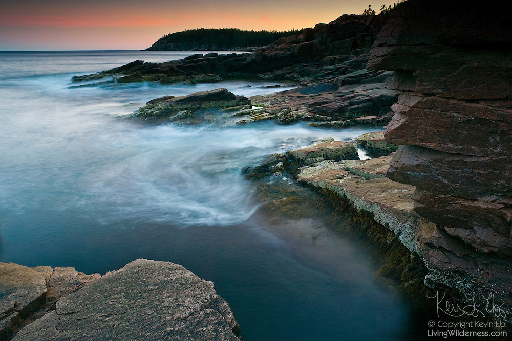 Atlantic Ocean waves crash into a narrow break in the rugged, granite shoreline of Acadia National Park, Maine. The ocean's waves are blurred by an extended exposure. Thunder Hole earns its name from stormy periods when waves slam into the tiny cove making a thunder-like sound.