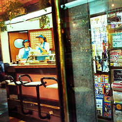 BUENOS AIRES, ARGENTINA:  Waitresses talk during their shift at a a local diner in Buenos Aires, Argentina. .(Photo by Ami Vitale)
