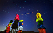 A meteor streaks across the sky with  Ugo Rondinone's Seven Magic Mountains art installation in the foreground during a Perseid<br /> meteor shower.